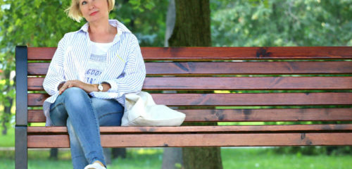 blond women sitting on a bench starting at the sky