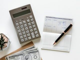 calculator, stack of US bills and a balance book referencing income