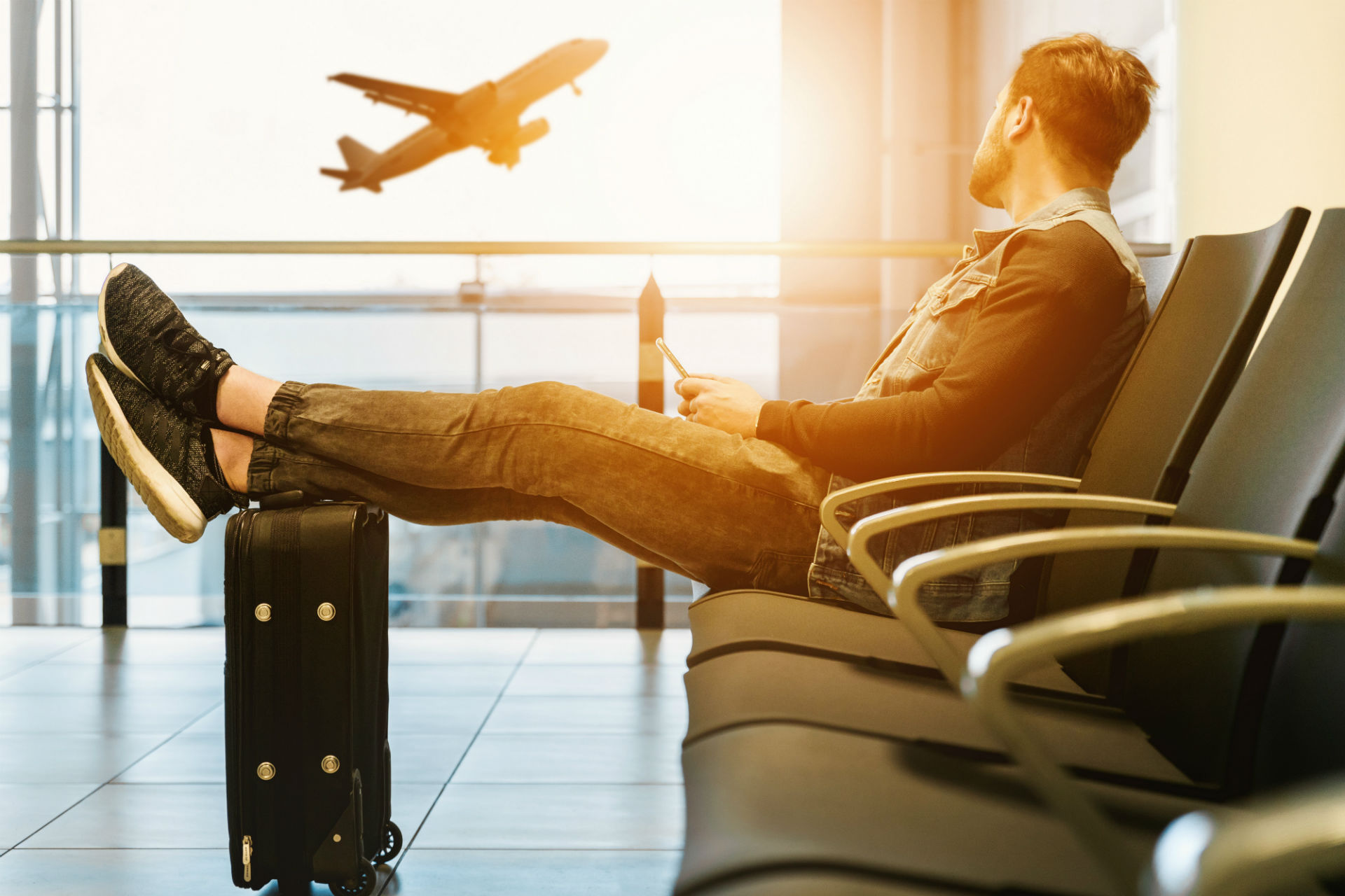 man sitting and watching an airplane take off