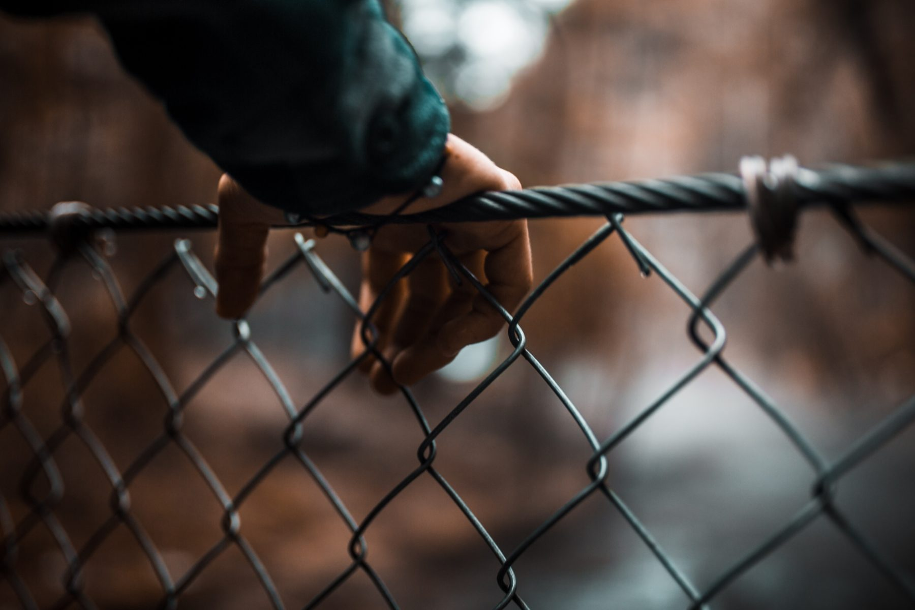 hand resting on top of a chain link fence