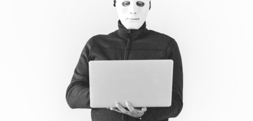 hacker with a face mask on holding a laptop