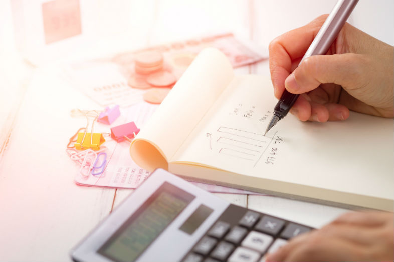 person using a calculator to determine tax and charitable giving allocation
