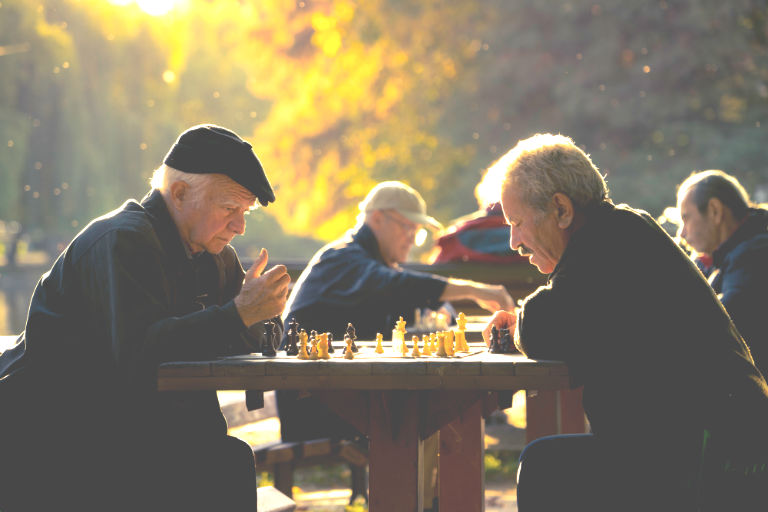 two retired men playing chess at the park