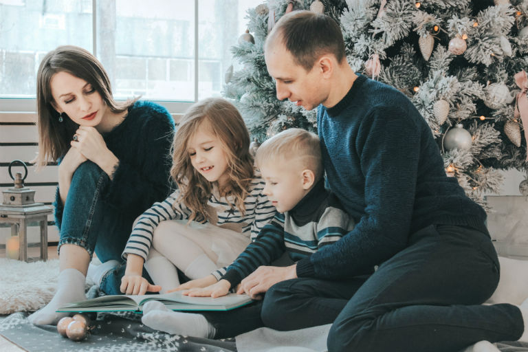 family of four reading a book around a christmas tree