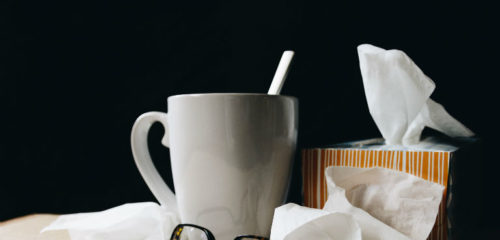 white ceramic mug on white table beside black eyeglasses