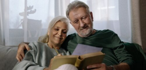 couple sitting on couch and smiling at IRA form
